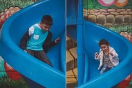 Kai and Kiari riding a slide down the Magic Maze